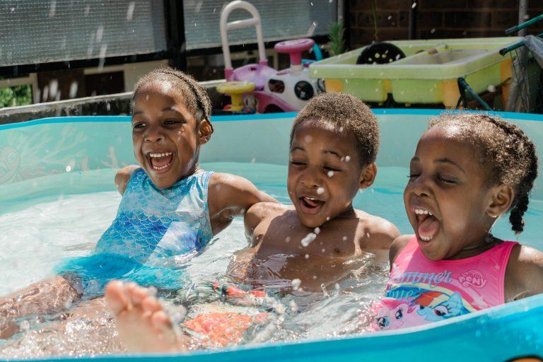 Bambini che fanno il bagno in una piscinetta gonfiabile